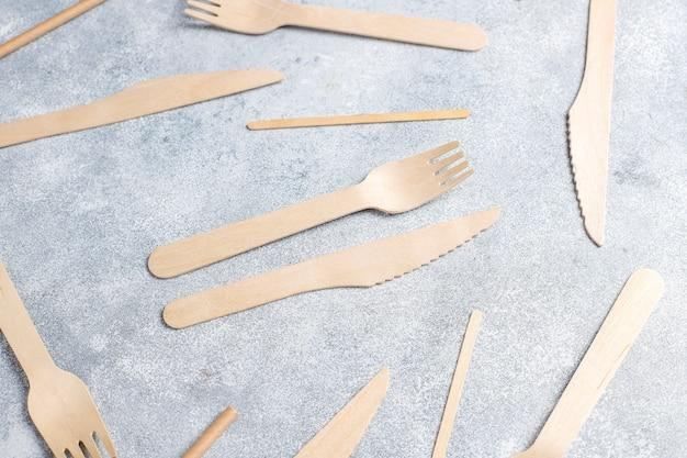 Umweltfreundliche einwegutensilien aus bambusholz und papier auf blauem grund. drapierte löffel, gabel, messer, bambusschalen mit pappbechern.