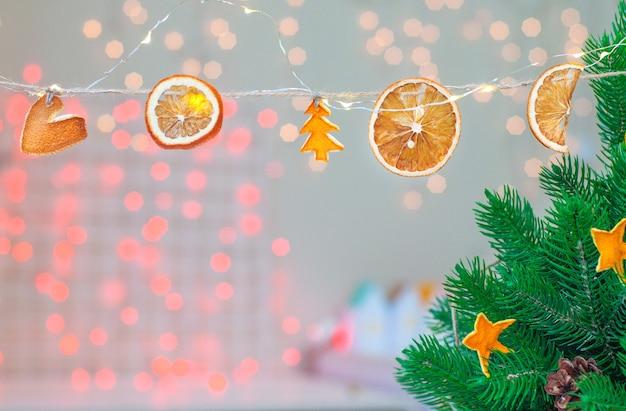 Umweltfreundliche handgemachte weihnachtsgirlande aus getrockneten zitrusscheiben auf bokeh-hintergrund.