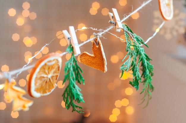 Umweltfreundliche handgemachte weihnachtsgirlande aus getrockneten zitrusscheiben. selektiver fokus auf das herz.