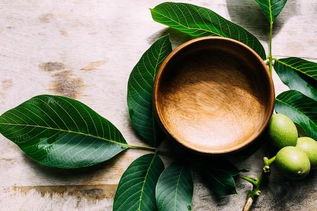 Umweltfreundliche hintergrundgrünblätter und eine holzschale auf dem tisch