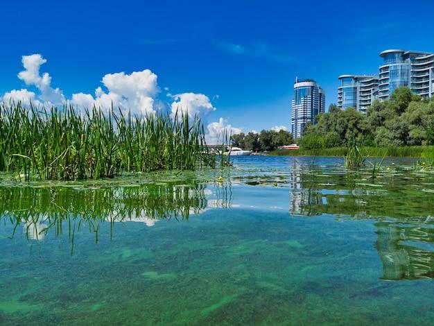 Umweltfreundliche landschaft mit blick auf die modernen, prestigeträchtigen apartmentkomplexe neben einem ökologisch sauberen see.