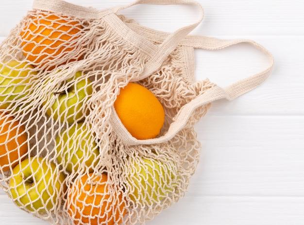Umweltfreundliche natürliche tasche mit früchten auf weißem holztisch
