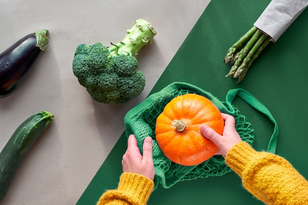 Umweltfreundliche null-abfall-wohnung lag mit händen, die brokkoli und saitentasche mit orangefarbenem kürbis hielten. flach lag mit gemüse und preiselbeeren im glas auf zweifarbigem hintergrund, braunem und grünem papier.