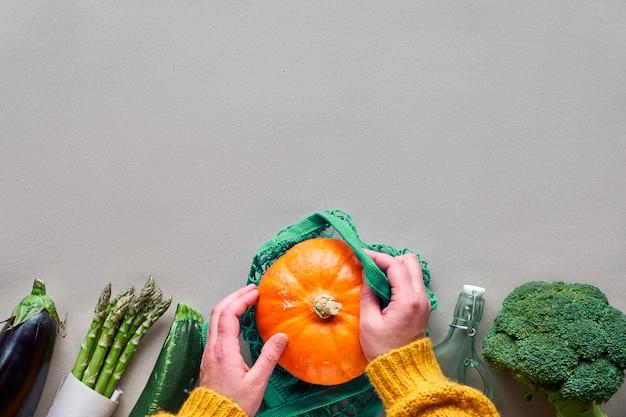 Umweltfreundliche null-abfall-wohnung lag mit händen, die brokkoli und saitentasche mit orangefarbenem kürbis hielten.