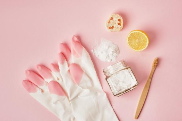 Umweltfreundliche reinigungskonzepthandschuhe bambuszahnbürste zitrone und soda auf rosa hintergrund