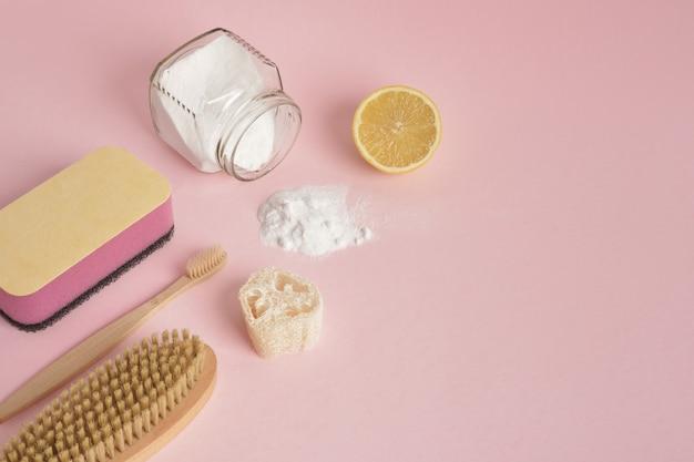 Umweltfreundliche reinigungskonzepthandschuhe holzbürstenschwamm zitrone und soda auf rosa hintergrund