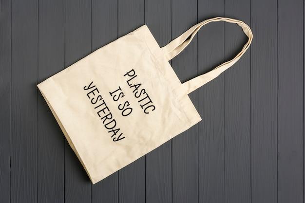 Umweltfreundliche vliestasche auf einem dunkelgrauen holztisch plastik ist gestern