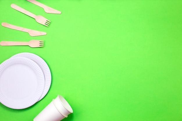 Umweltfreundliche wegwerfgeräte hergestellt vom bambusholz und vom papier auf einem grünen hintergrund.