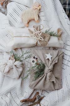 Umweltfreundliche weihnachtsgeschenkverpackung im traditionellen japanischen furoshiki-stil auf einem gestrickten weißen hintergrund. geschenke mit eigenen händen einpacken.
