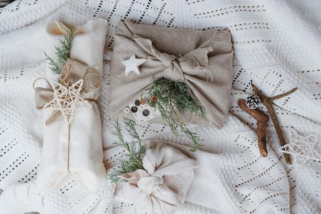 Umweltfreundliche weihnachtsgeschenkverpackung im traditionellen japanischen furoshiki-stil auf einer gestrickten weißen wand. geschenke mit eigenen händen einpacken. günstiges neues jahr.
