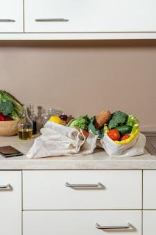 Umweltfreundliche wiederverwendbare baumwolltaschen mit obst, gemüse und brot auf dem küchentisch. null-abfall-konzept. nachhaltiger lebensstil