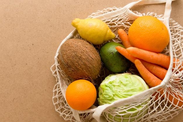 Umweltfreundliche, wiederverwendbare einkaufstasche aus maschenstrick mit obst und gemüse, ohne abfall