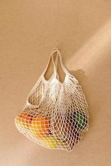 Umweltfreundliche, wiederverwendbare einkaufstasche aus maschenstrick mit obst und gemüse