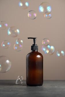 Umweltfreundlicher braunglas-seifenspender mit pumpflasche gefüllt mit spülseife oder duschgel auf dunklem ...