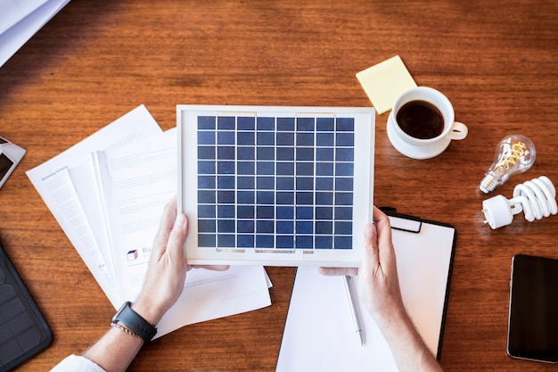 Umweltfreundlicher ingenieur, der ein solarpanel hält