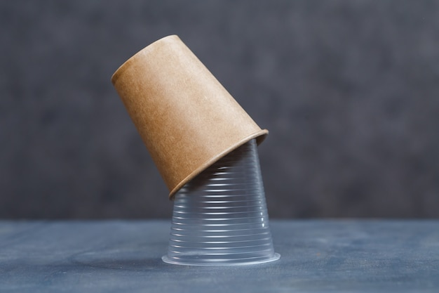 Umweltfreundliches einweggeschirr aus bambusholz und papier auf grauem grund. geschirr und besteck aus plastik. für die umwelt sorgen. recyclingproblem. sicherer planet, umweltkonzept.