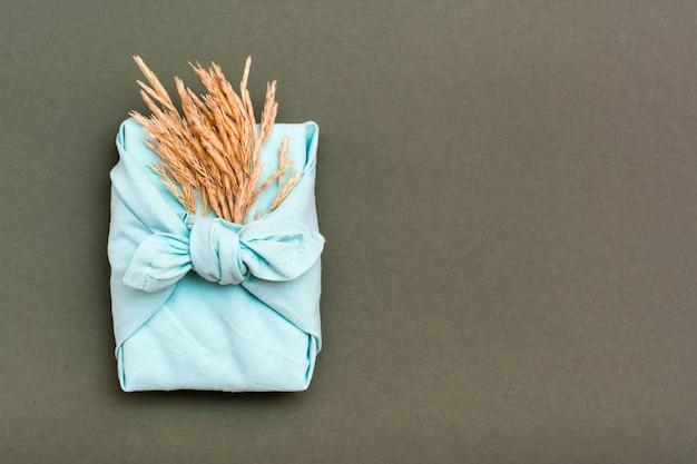 Umweltfreundliches furoshiki-geschenk mit ohren des trockenen grases auf grünem hintergrund