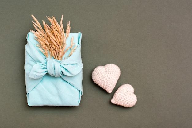 Umweltfreundliches furoshiki-geschenk mit ohren des trockenen grases und zwei gestrickten herzen auf einem grünen hintergrund