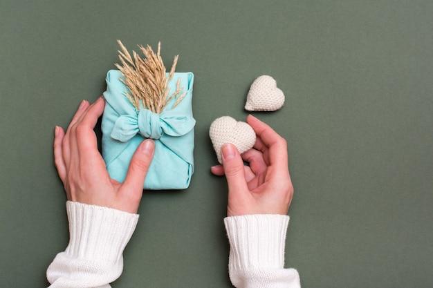 Umweltfreundliches geschenk für furoshiki zum valentinstag und gestrickte herzen in den weiblichen händen auf einem grünen hintergrund