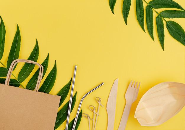 Umweltfreundliches set mit bambus, einweggeschirr aus papier und metallstrohhalmen auf gelb
