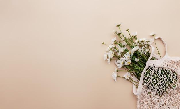 Umweltfreundliches sommerkonzept auf beigem hintergrund mit öko-einkaufstaschenblumen