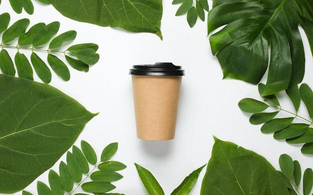 Umweltfreundliches stillleben. einweg-kaffeetasse aus pappkarton auf weißem hintergrund mit grünen tropischen blättern.