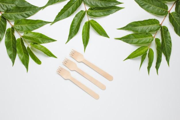 Umweltfreundliches stillleben. wegwerfholzgabeln auf einem weißen hintergrund mit grünen tropischen blättern. besteck aus natürlichen materialien