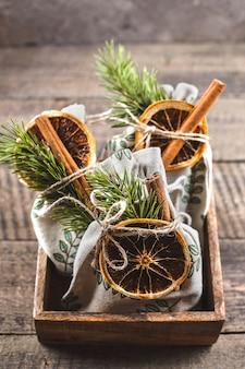 Umweltfreundliches textilweihnachtsgeschenk in holzkiste. zero waste weihnachten. geschenkbeutel aus stoff, verziert mit tannen, trockenen zitrusfrüchten und zimtstangen.