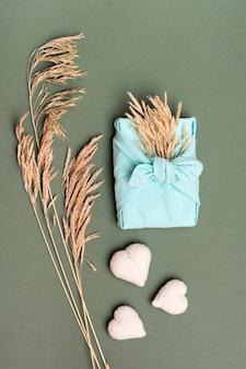 Umweltfreundliches valentinstaggeschenk furoshiki, gestrickte herzen und ohren des trockenen grases auf grünem hintergrund. vertikale ansicht