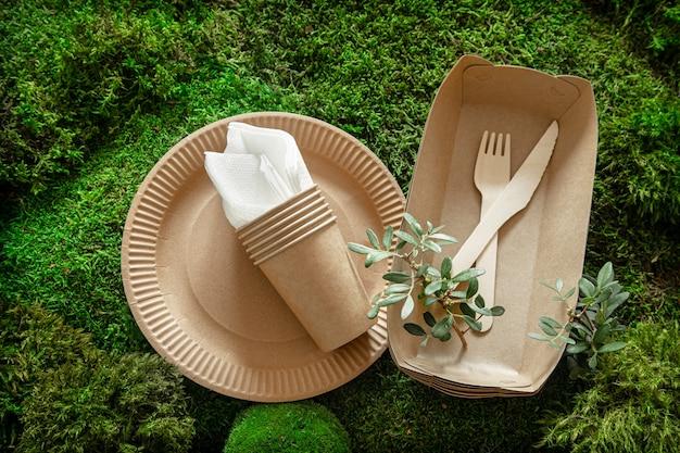 Umweltfreundliches, wegwerfbares, recycelbares geschirr. papiernahrungsmittelkästen, teller und besteck der maisstärke auf einem grünen grashintergrund.