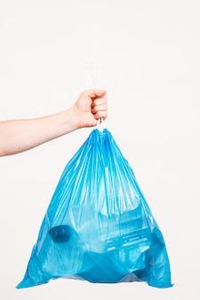 Umweltschutz. mannhand hält blaue plastiktüte voll mit müll, auf weißem hintergrund