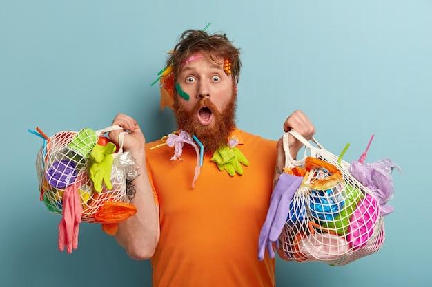 Umweltschutzkonzept. verwirrter schockierter rothaariger bärtiger mann starrt, erstaunt über die naturkatastrophe, plastikmüll, modelle über blauer wand mit zwei müllsäcken