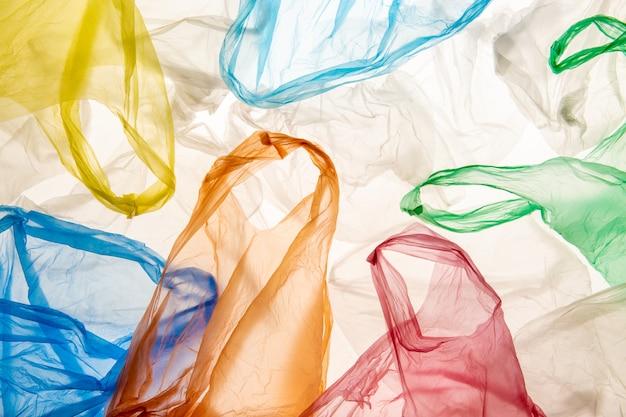 Umweltverschmutzungskonzept mit leerem faltigem verwendetem hintergrundbeleuchtetem buntem plastiktütenmuster lokalisiert auf weißem hintergrund
