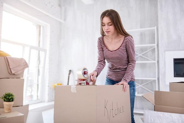 Umzug. charmante junge frau mit klebeband, um eine box mit küchenbesteck zu versiegeln, während sie sich für den auszug fertig machen