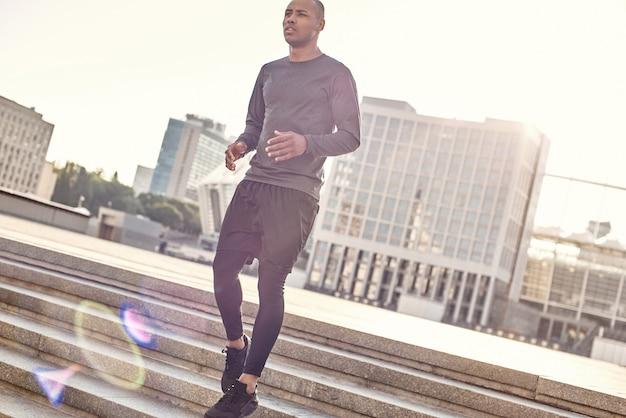 Umzug ist eine lebensweise in voller länge porträt eines sportlichen afrikanischen mannes in sportbekleidung