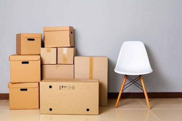 Umzugskartons mit gepackten sachen und stuhl zum umziehen