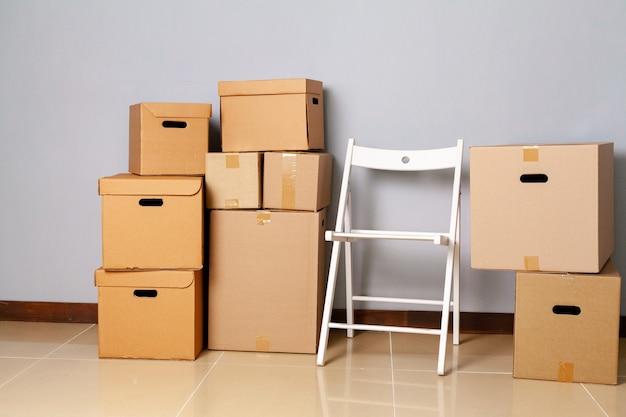 Umzugskartons mit verpacktem material und stuhl zum umzug