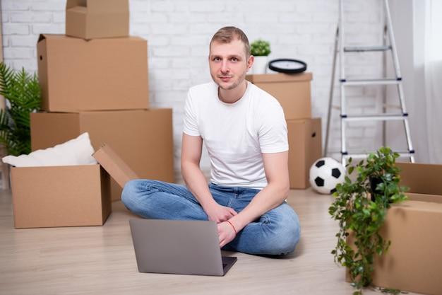 Umzugstag - junger gutaussehender mann mit laptop in neuen wohnungen, umgeben von kartons