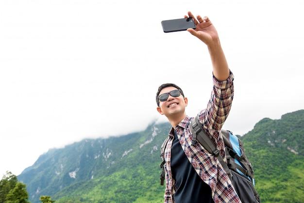 Unabhängiger asiatischer touristischer mann, der selfie mit natürlicher grüner gebirgslandschaft nimmt