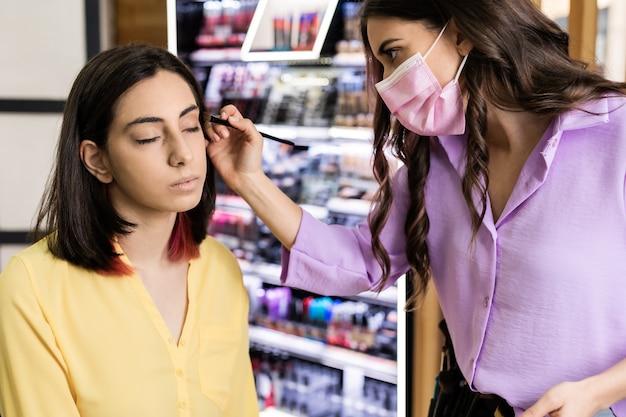 Unabhängiger maskenbildner, der einer jungen hispanischen frau, die mit einer medizinischen maske für covid19 geschützt ist, kosmetik aufträgt