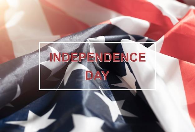 Unabhängigkeitstag-inschrift über usa-flagge. 4. juli-karte mit worten über der amerikanischen flagge.