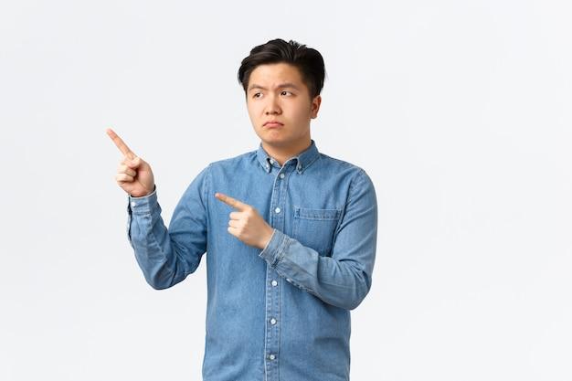 Unamüsierter und enttäuschter asiatischer düsterer mann in blauem hemd, verärgert die stirn runzelnd und zeigt mit den fingern auf die obere linke ecke, beschwert sich über schlechtes produkt, fühlt sich beunruhigt, steht auf weißem hintergrund