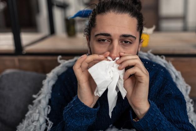 Unangenehme krankheit. porträt eines traurigen kranken mannes, der dich anschaut, während er an der laufenden nase leidet