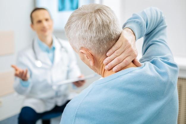Unangenehmer schmerz. netter gut aussehender alter mann, der seinen arm hebt und seinen nacken hält, während er dort schmerzen spürt