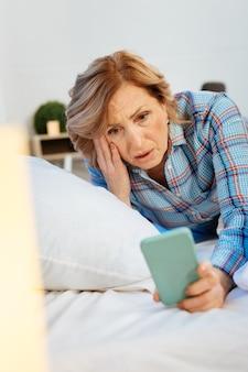Unangenehmes aussehen. ausdrucksstarke hellhaarige frau, die einen karierten pyjama trägt und das smartphone beim aufwachen inspiziert