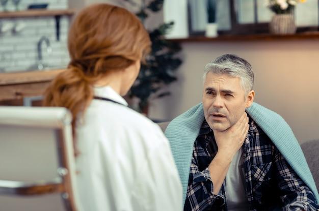Unangenehmes gefühl. unglücklicher kranker mann, der seinen hals hält, während er halsschmerzen hat