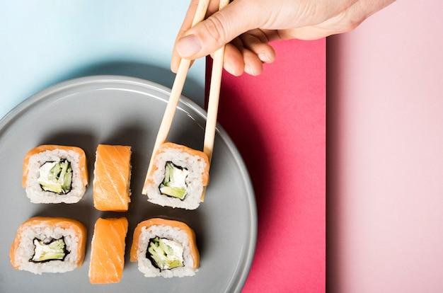 Unbedeutende platte mit sushirollen und essstäbchen