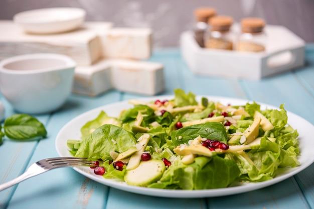 Unbedeutender gesunder salat mit gabel und unscharfem hintergrund