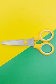 Unbedeutendes foto der schere der gelben kinder auf gelbem und grünem hintergrund. flacher, vertikaler schuss einer gelben schere mit zentraler komposition