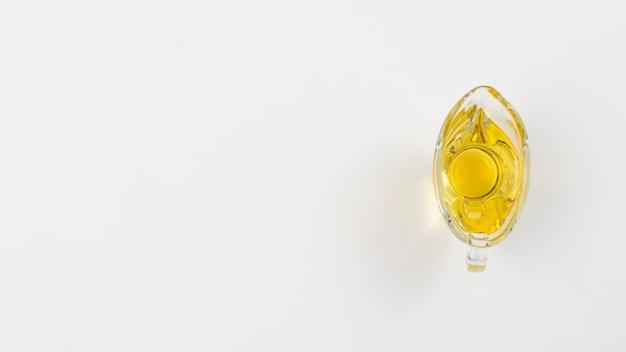 Unbedeutendes olivenöl in einem glas mit weißem kopienraumhintergrund